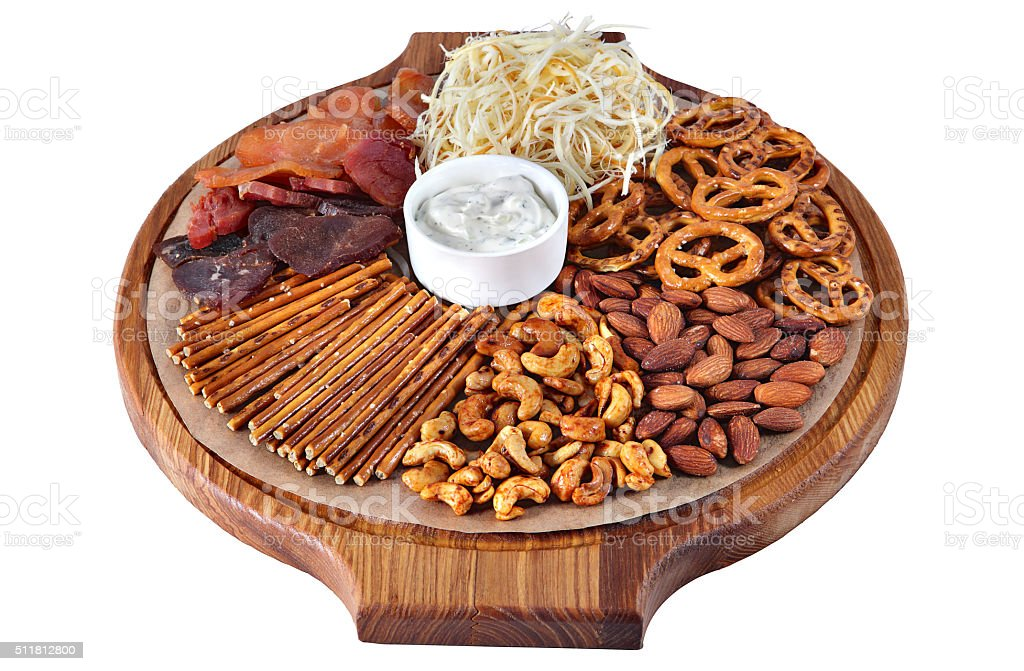 Mix of beer snacks on round wooden board stock photo