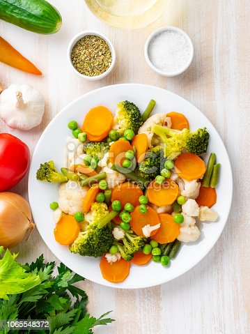 Mix of boiled vegetables, steam vegetables for dietary low-calorie diet. Broccoli, carrots, cauliflower, top view, vertical.