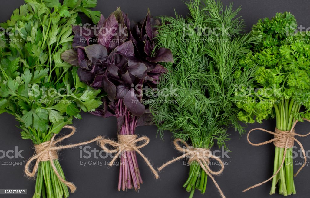 Mix of bunches of fresh spicy herbs tied with a rope on a black table...