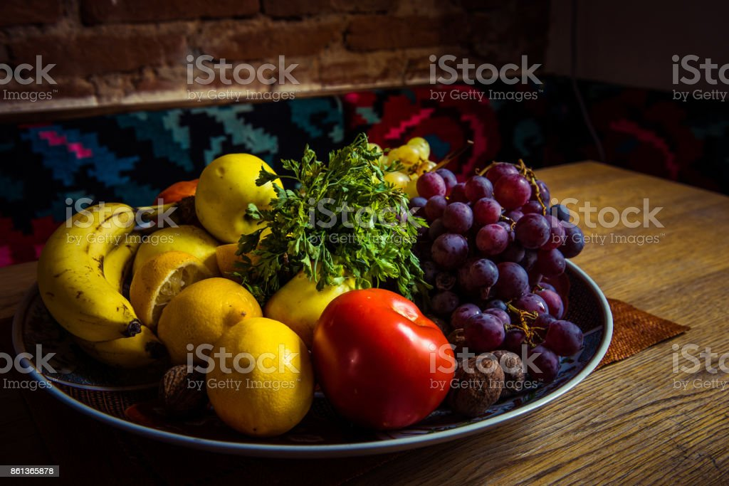 Mix of delicious fruits in a plate on a wooden table stock photo