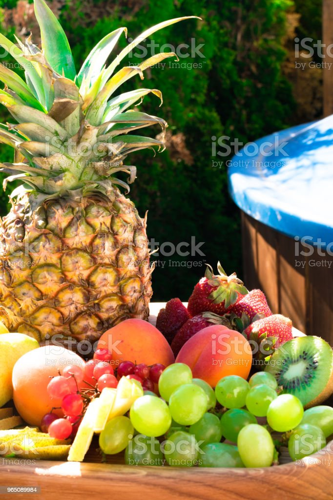 Mix of different exotic fresh colorful fruits on dark wooden table and green trees royalty-free stock photo