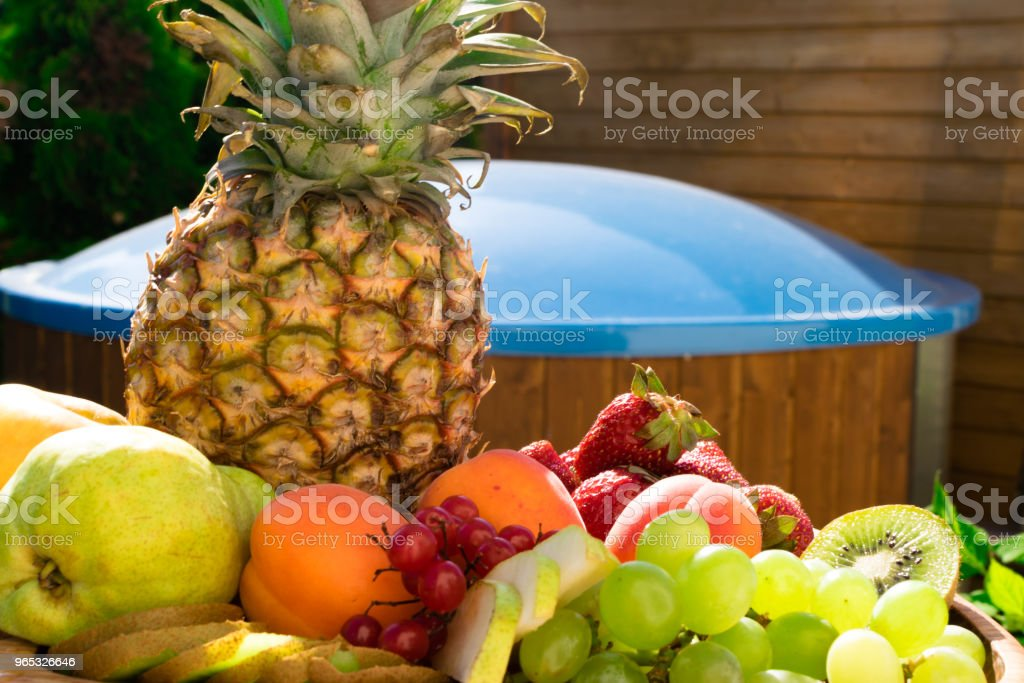 Mix of different exotic fresh colorful fruits on dark wooden table and green trees zbiór zdjęć royalty-free