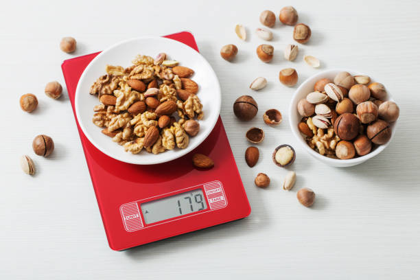 mix of different nuts on  kitchen scale on a white table stock photo