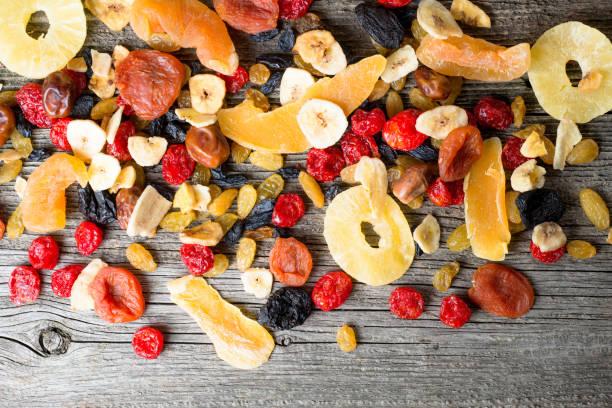 ahşap bir arka planda kurutulmuş ve meyveli meyve karışımı, üst görünüm - kuru meyve stok fotoğraflar ve resimler
