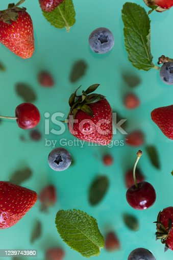 879258868 istock photo mix of flying berries on a blue background 1239743980