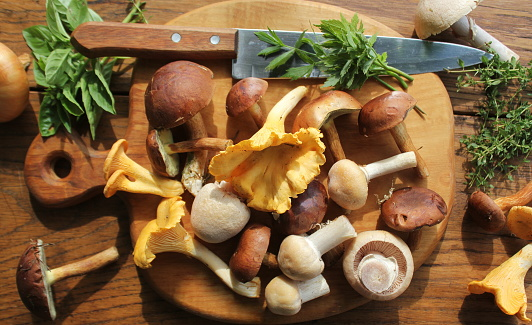 Mix of forest mushrooms on cutting board over old wooden table .