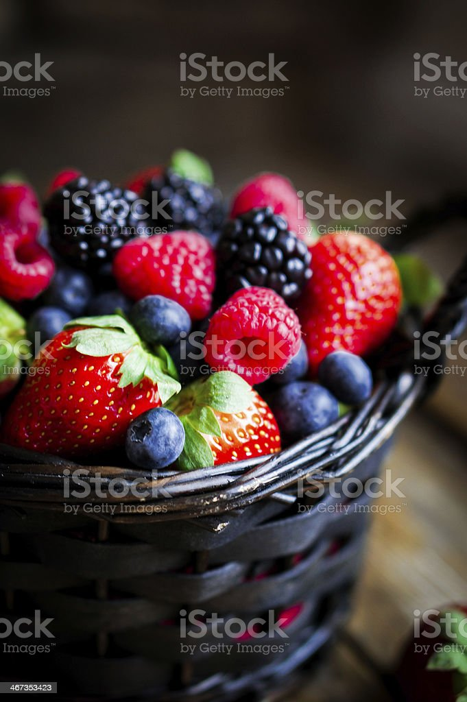 Mix of fresh berries in a basket on wooden background stock photo