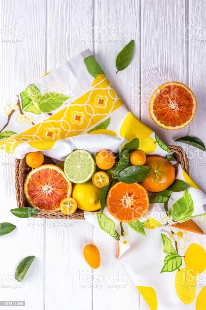Mix of fresh citrus fruits in basket. Orange, lemon, mandarin, lime, kumquat on white wooden background photo libre de droits