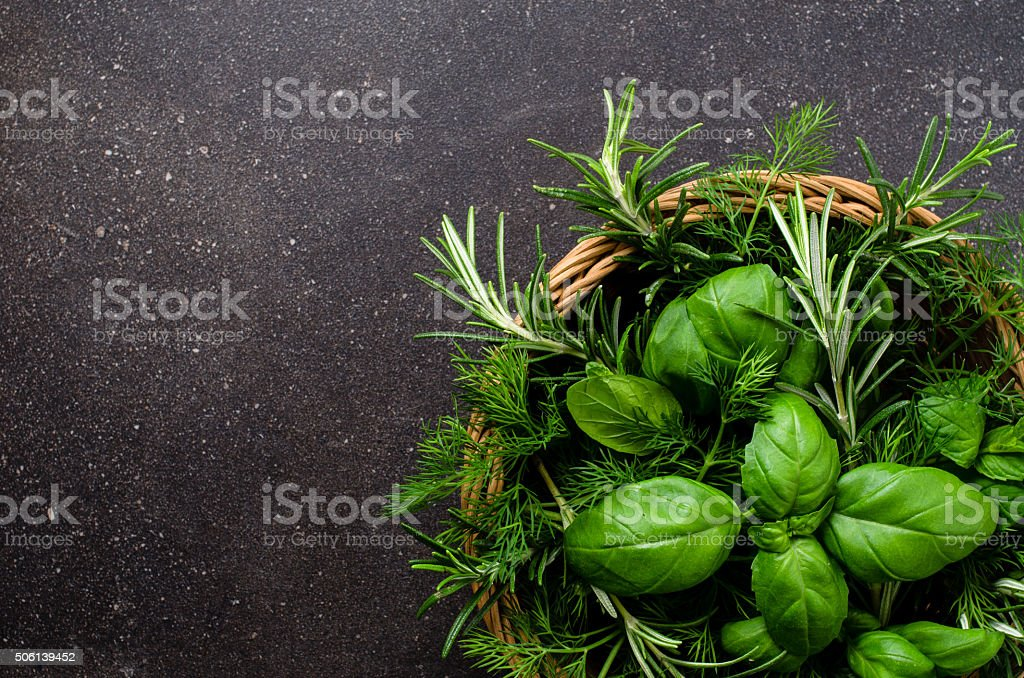 Mix of fresh herbs in wicker basket stock photo