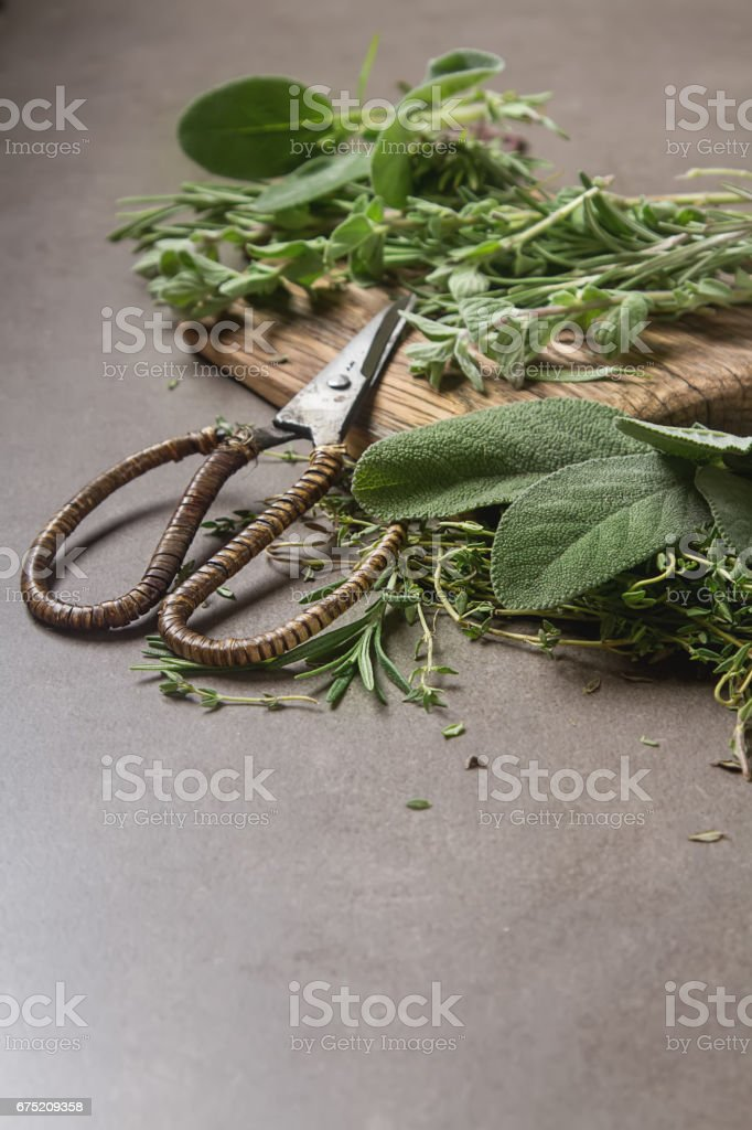 Mix of fresh Italian herbs from garden on an old table. Rosemary, temyan, oregano. Dark background. royalty-free stock photo