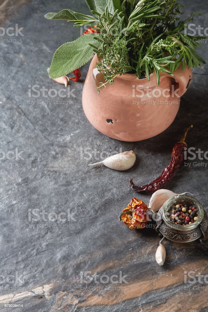 Mix of fresh Italian herbs from garden on an old table. Rosemary, temyan, oregano. Dark background. Dry chili. royalty-free stock photo