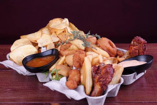 Mix of fried potatoes and wurstel - foto stock