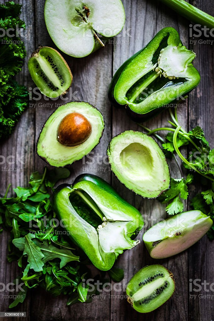 Mix of green vegetables and fruits on rustic background stock photo