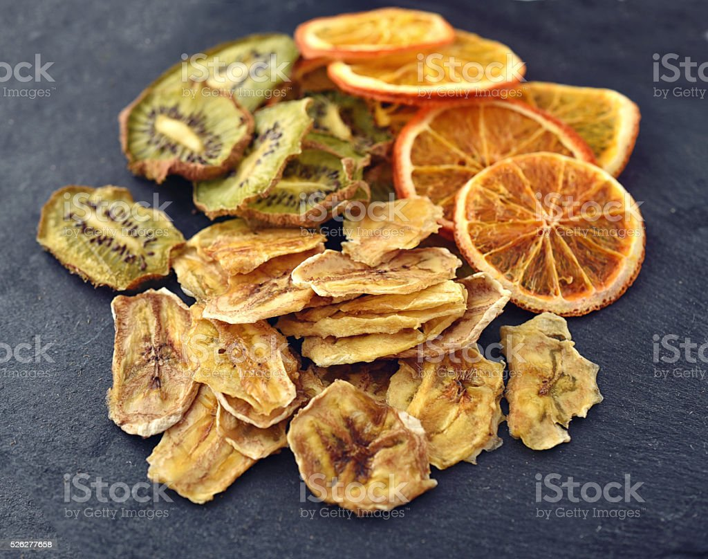 Mix of Homemade Fruit chips on black slate surface stock photo