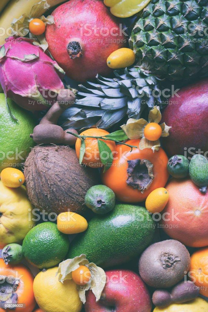 Mix of ripe tropical fruits with avocado mango, kumquat, kiwi, citrus. Superfood background. Vegetarian raw food. Copy space stock photo
