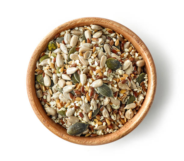 mix of seeds in wooden bowl mix of seeds in wooden bowl isolated on white background, top view seed stock pictures, royalty-free photos & images