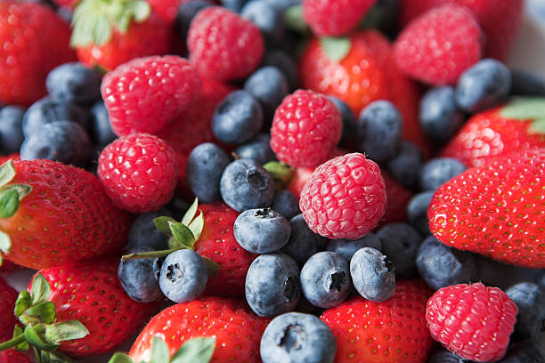 A mix of strawberries, blueberries, and raspberries stock photo