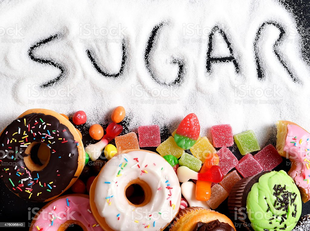 mix of sweet cakes, donuts and candy with sugar text mix of sweet cakes, donuts and candy with sugar spread and written text in unhealthy nutrition, chocolate abuse and addiction concept, body and dental care 2015 Stock Photo