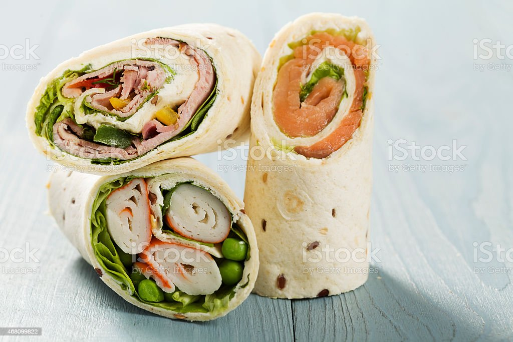 Mix of wraps with ham, chicken, salmon and crab served stock photo