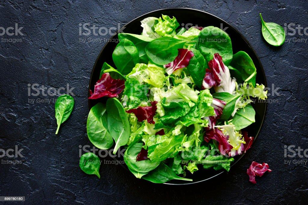 Salatblätter in einer schwarzen Schüssel mischen – Foto