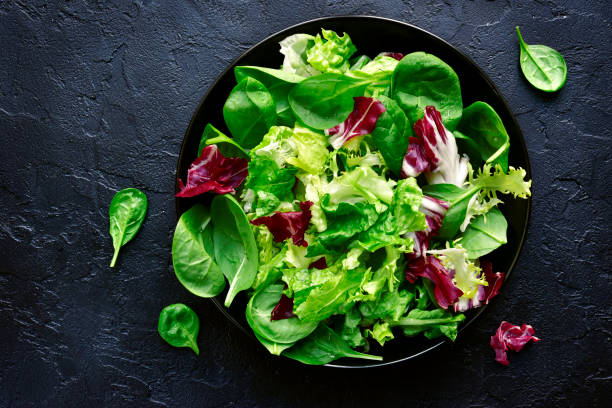 mix salad leaves in a black bowl - lettuce stock photos and pictures