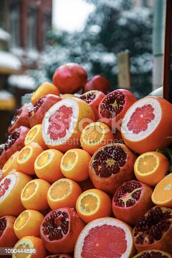 Healthy winter produce pomegranates, oranges and grapefruits waiting for make juice recipes at the street market in snowy winter day