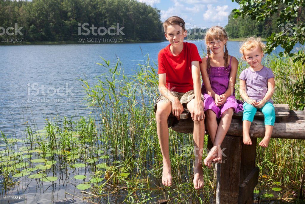Mixed age children sitting on a pier by a summer lake stock photo