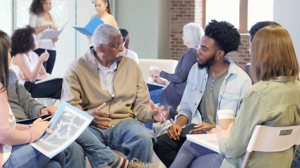 Mixed age group discusses racial issues A multi-ethnic, multi generational group openly discusses the racial issues dividing their community. community center stock pictures, royalty-free photos & images