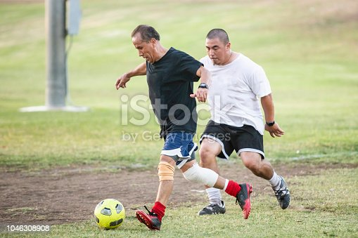 A mature mexican man and a younger man battle for the ball in a soccer game