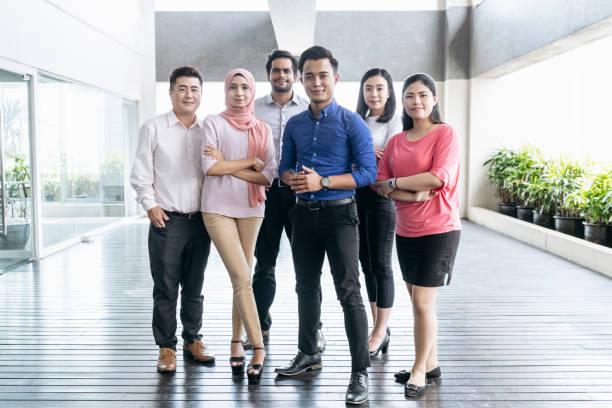 colegas de trabalho de gama de idade mista no escritório moderno - malásia - fotografias e filmes do acervo