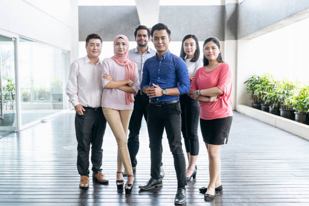 Mixed age range business colleagues in modern office Multi racial group standing facing camera and smiling business Malaysia stock pictures, royalty-free photos & images