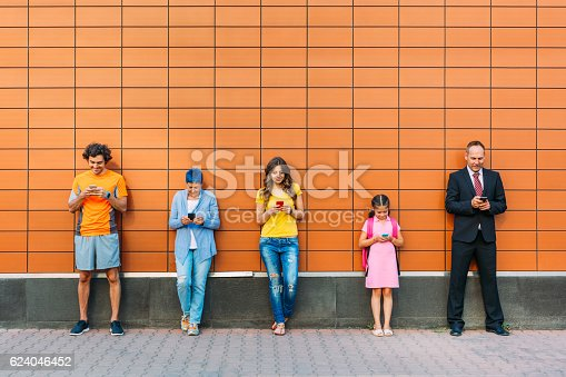 Group of different generation people standing against a wall and text messaging, social media and communication concept.