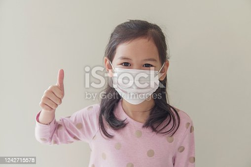 Mixed Asian student  girl wearing mask and giving thumb up, school reopening, return back to school after covid-19 coronavirus pandemic is over, new normal concept