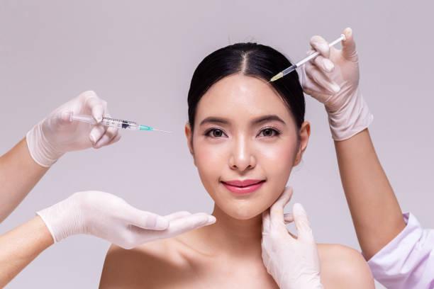 Gemischte asiatische junge 20er Jahre Frau geht durch die Haut Pflege und Ästhetik medizinische Therapie und durch die Hände des Arztes mit Spritzen in weißem Hintergrund injiziert werden. – Foto