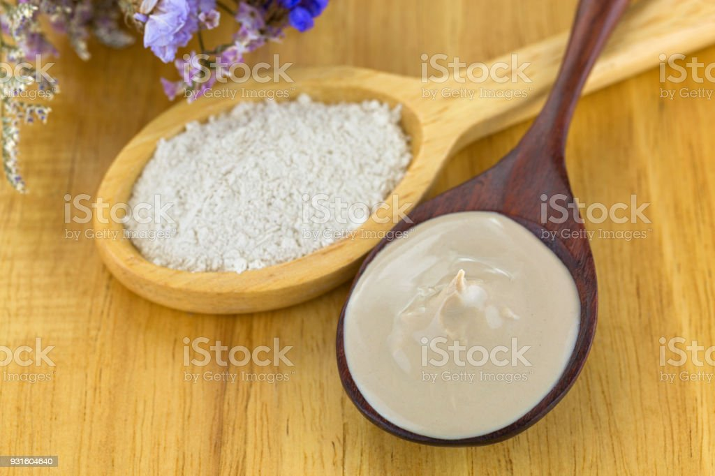 Mixed Australian Clay Powder ready to mask skin, next to dried powdery clay in wooden spoon stock photo