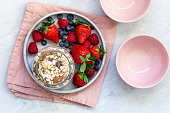 Mixed berries in conrete plate on marble background with empty plate and copy space