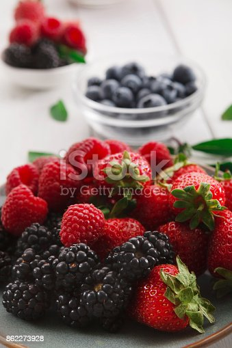 862604802 istock photo Mixed berries in glass bowls closeup, selective focus 862273928