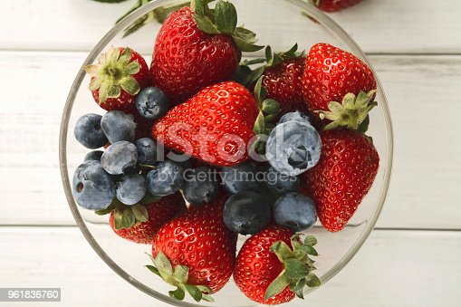 862604802 istock photo Mixed berries in glass bowls closeup, top view 961836760