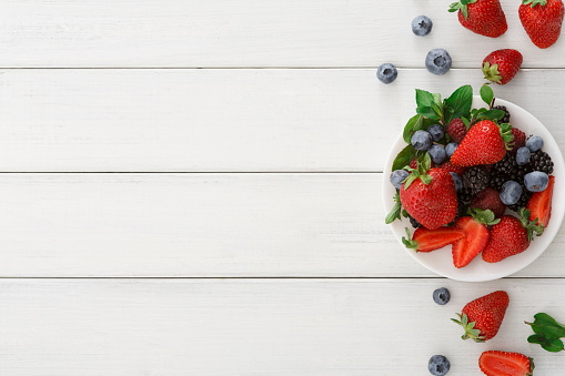 istock Mixed berries in glass bowls on white wooden table top view 859662448