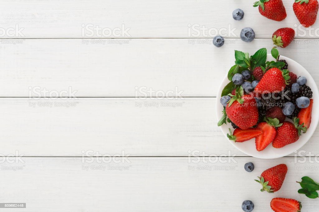 Mixed berries in glass bowls on white wooden table top view stock photo