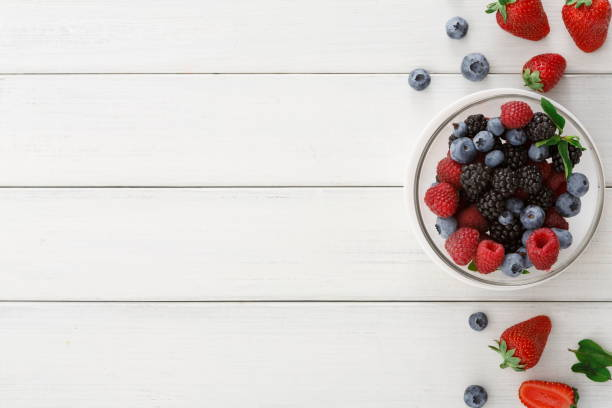 mixed berries in glass bowls on white wooden table top view - berry stock photos and pictures