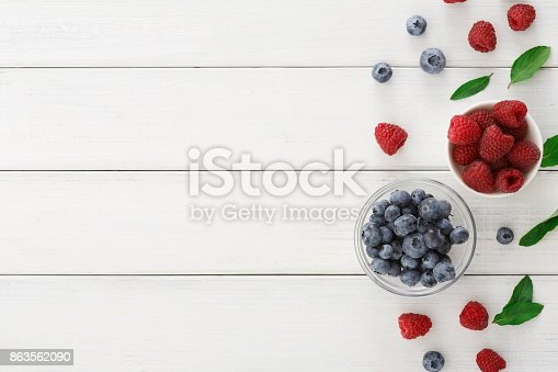 istock Mixed berries in glass bowls on white wooden table top view 863562090