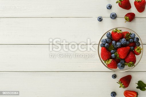 862604802 istock photo Mixed berries in glass bowls on white wooden table top view 965503064