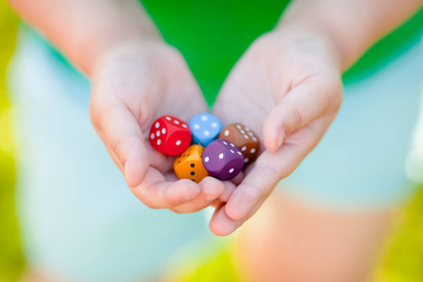 Mixed color dices in child's hands. stock photo