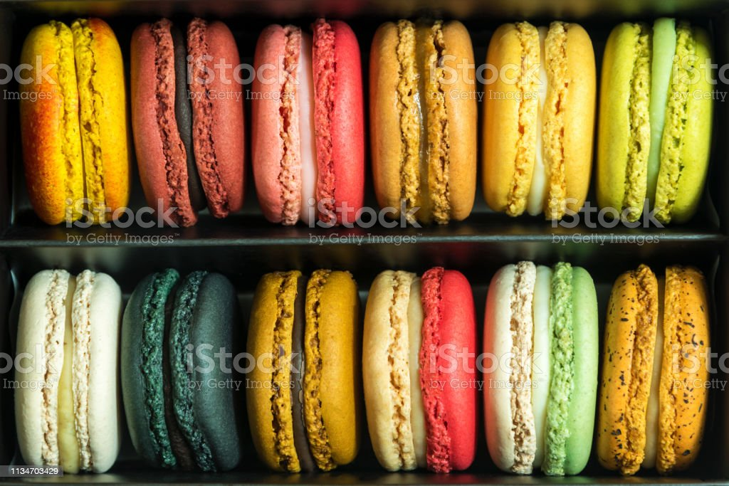 Mixed colorful french macaroons in box. Sweet food pattern background.