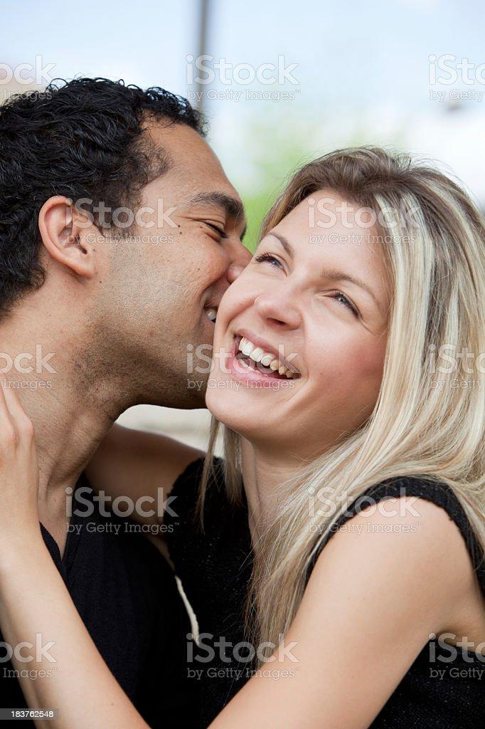 Mixed couple kissing stock photo