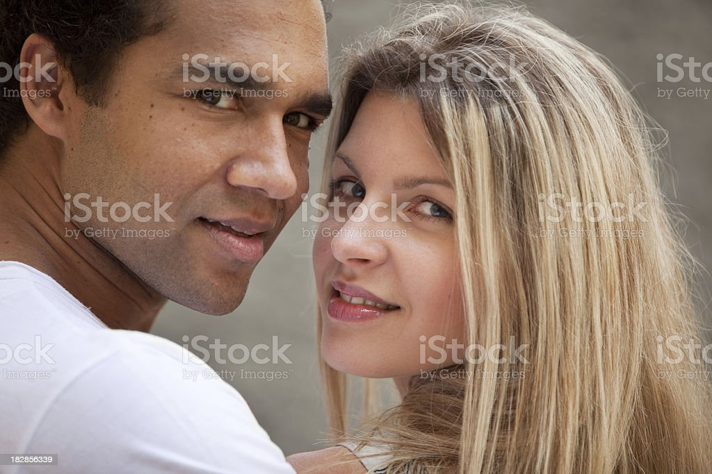 Mixed couple looking over their shoulders stock photo