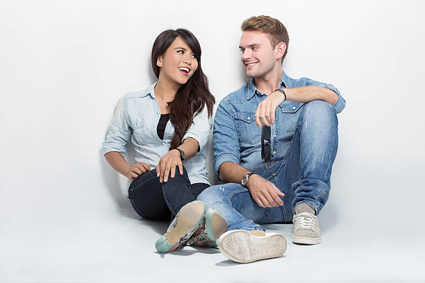 Mixed couple sitting on the floor. man embracing woman stock photo