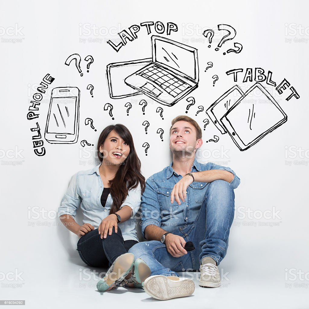 Mixed couple thinking about electronic between cellphone, laptop stock photo