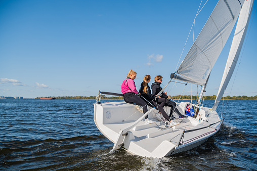 A mixed crew of a sports yacht participates in sailing competitions on the river. One man and two girls